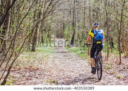 Young active man cycling in spring forest - stock photo