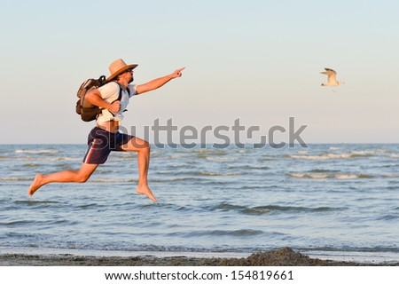 Young active man with backpack jumping high looking up and running at seashore on the summer outdoors background