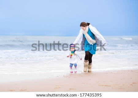 Young active mother and her cute toddler daughter running together on a beautiful windy winter beach in Holland - stock photo