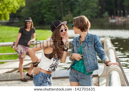 Young active people. Two woman and one man are flirting. Outdoors, lifestyle - stock photo