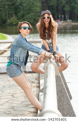 Young active people. Two young woman having fun near the river. Outdoors, lifestyle