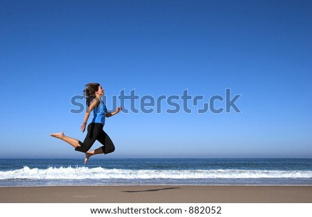 Young active woman alone in the beach doing some morning sports, running and jumping in the beach.