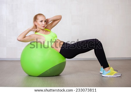 Young active woman doing pilates exercises in fitness studio