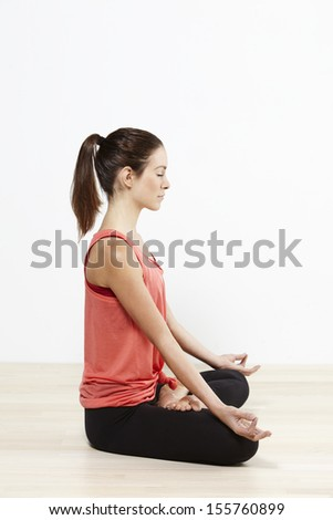 Young active woman doing yoga. The lotus position