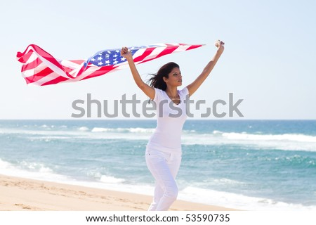 young active woman holding american flag and running on beach - stock photo