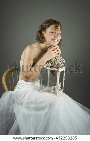 Young actress ballerina in a white tutu and a beautiful cage with a figure of a bird inside, isolated in a grey background