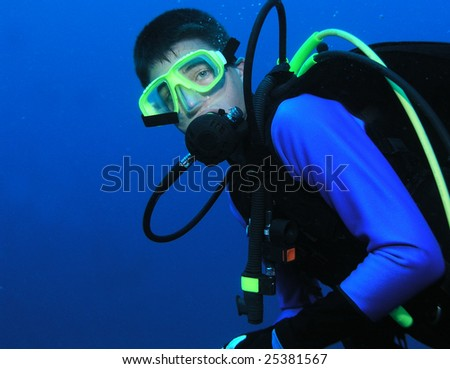 Young adolescent scuba diver poses at depth all geared up in scuba equipment