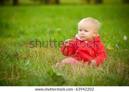 young adorable baby sit on grass in park touching grass and flowers