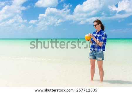 Young adorable cheerful woman in cotton checked shirt and sunglasses enjoying coconut cocktail with drinking straw against turquoise sea at tropical white sandy beach during her Caribbean vacation - stock photo