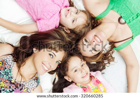 Young adorable hispanic girls and mothers lying down with heads touching and bodies spread out different directions closeup.