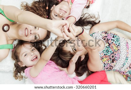 Young adorable hispanic sisters and mother lying down with heads touching and bodies spread out different directions closeup. - stock photo