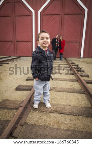 Young Adorable Mixed Race Boy at Train Depot with Parents Smiling Behind.