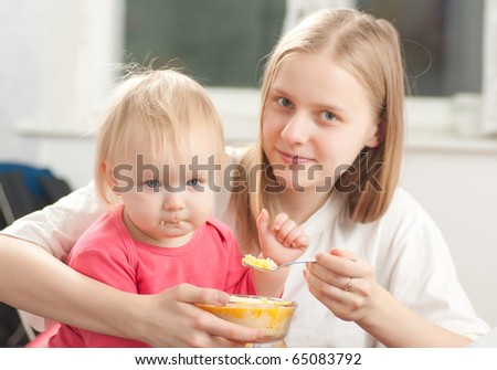 young adorable mother feeding his daughter with porridge - stock photo