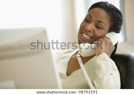 Young adult African American woman at desk talking on phone - stock photo