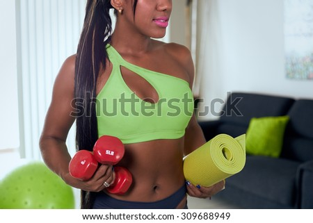 Young adult african american woman in sports clothing at home, preparing herself for doing domestic fitness with weights. Cropped view waist up - stock photo