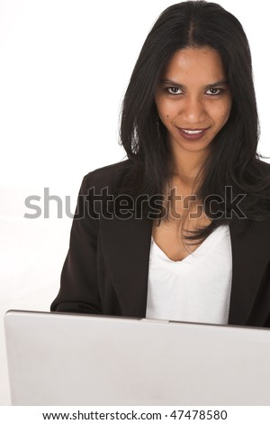 Young adult African-Indian businesswoman in casual office outfit sitting with a laptop computer on her lap on a white background. Not Isolated
