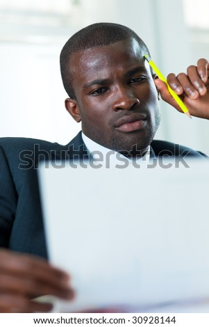 young adult afro-american businessman examining documents indoors - stock photo