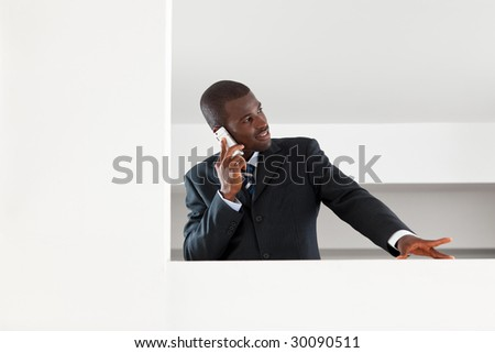 young adult afro-american businessman talking on the phone indoors. Copy space