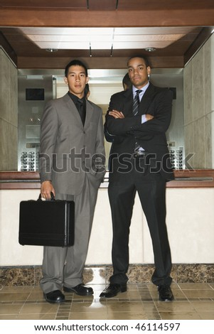 Young adult Asian and African-American businessmen standing in an office lobby looking at the camera. Vertical format. - stock photo
