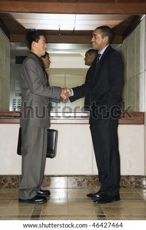 Young adult Asian and African-American businessmen standing in an office lobby shaking hands. - stock photo