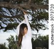 Young adult Asian female hanging from a tree looking at viewer. - stock photo