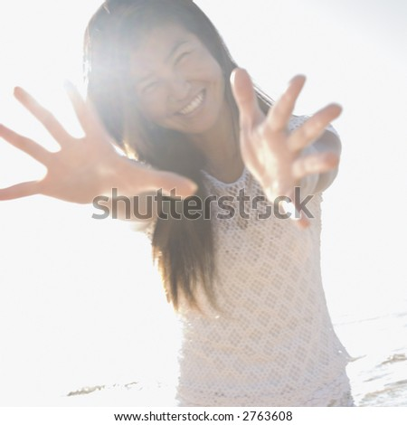 Young adult Asian female with arms and hands stretched out toward viewer. - stock photo