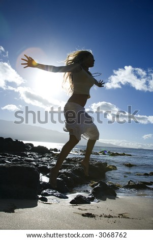 Young adult Asian Filipino female jumping on beach in Maui Hawaii. - stock photo