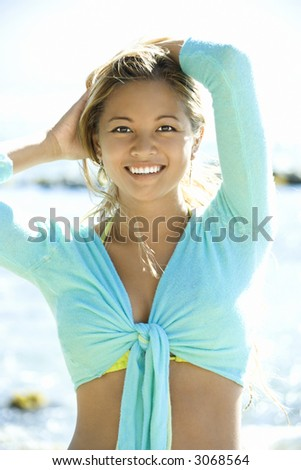 Young adult Asian Filipino female looking at viewer smiling with arms raised on beach in Maui Hawaii. - stock photo