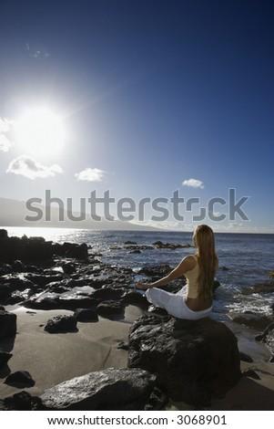 Young adult Asian Filipino female meditating on rocky beach in Maui Hawaii. - stock photo