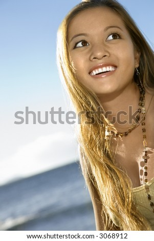 Young adult Asian Filipino female smiling on beach in Maui Hawaii. - stock photo