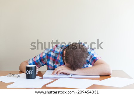 young adult asleep over books holding a cup. - stock photo