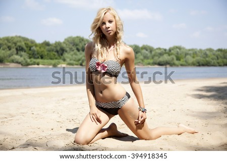 Young adult attractive beautiful blonde woman in bikini on the beach - stock photo
