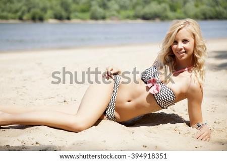 Young adult attractive beautiful blonde woman in bikini on the beach