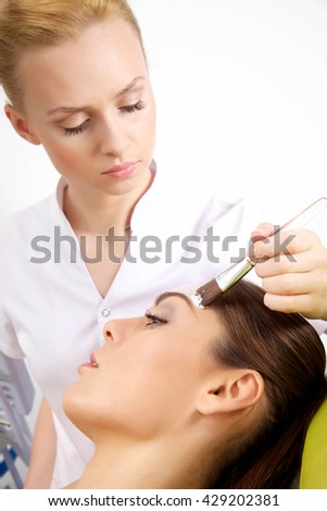 Young adult attractive pretty woman getting beauty skin mask treatment on her face with brush