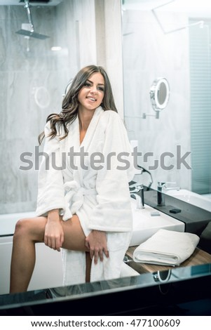 Young adult attractive woman standing in front of bathroom mirror and taking care of herself after warm bath in hotel room. Toned image.