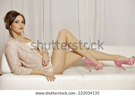 Young adult beautiful and attractive female brunette pretty woman posing in pink lingerie on the white sofa in luxury style apartment - stock photo