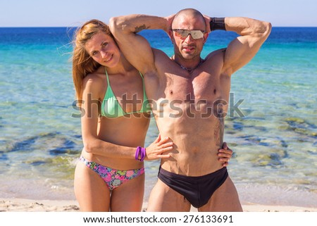Young adult beautiful couple relaxing on beach. The couple