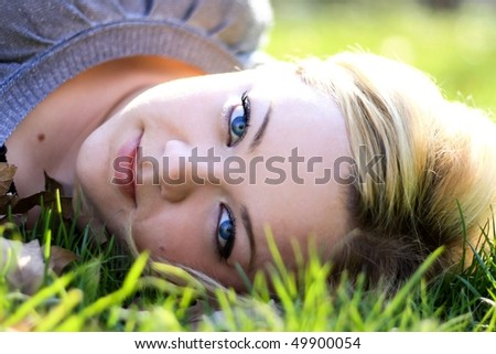 Young adult beautiful girl lying in grass
