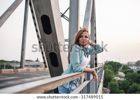 young adult beautiful woman standing on bridge , holding her hairs with hands - stock photo