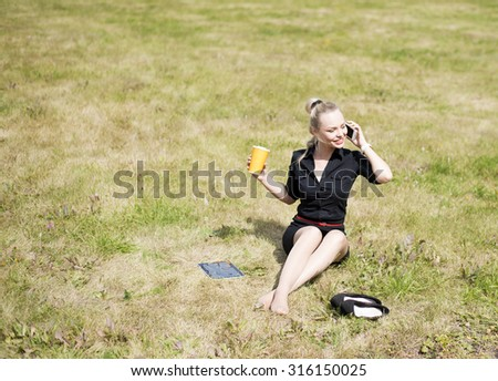 young adult blond caucasian business Woman using mobile cell phone  in city park Businesswoman lie on summer fresh green grass outdoor Coffee cup hold in hand and tablet computer stand near - stock photo