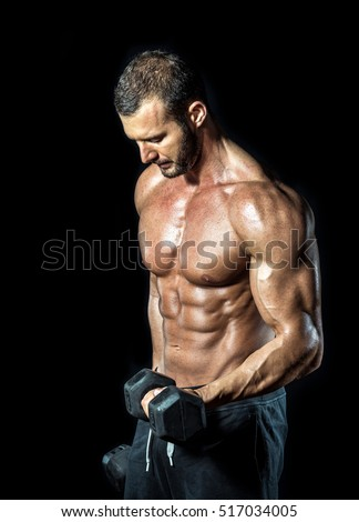 Young adult bodybuilder doing standing biceps curls isolated on black background.