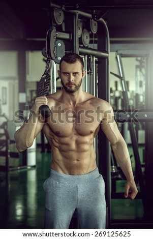 Young adult bodybuilder doing triceps overhead extension rope exercise - stock photo