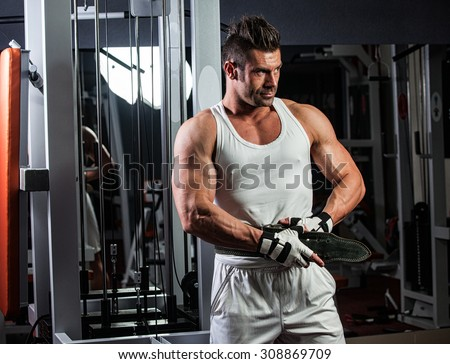 Young adult bodybuilder doing weight lifting in gym. - stock photo