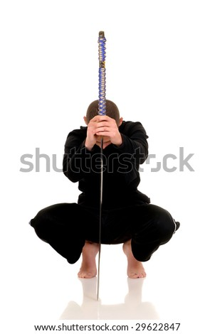 young adult boy practicing the martial art of the samurai warriors, studio shot - stock photo