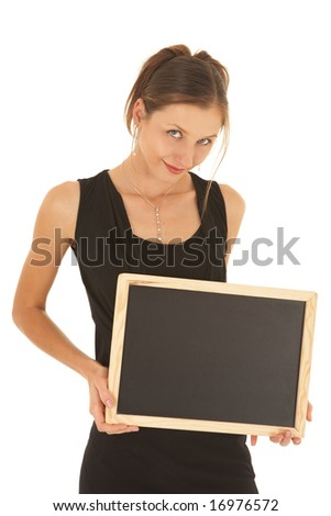 Young adult brunette businesswoman in a black office outfit on a white background, holding an empty blackboard