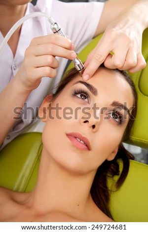 Young adult brunette pretty woman getting laser face treatment in medical spa center, skin rejuvenation concept - stock photo