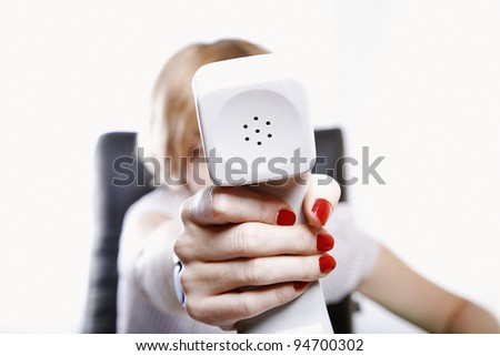 young adult business woman holding telephone receiver in hand, focus on the tube closeup, toned image - stock photo