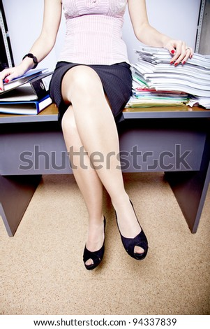 young adult business woman sitting on a table among the piles of papers and documents - stock photo