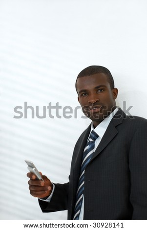 young adult businessman holding mobile phone. Shadows from venetian blinds on wall. Copy space - stock photo