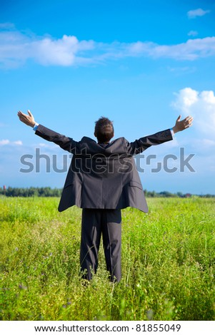 young adult businessman in a field with outstretched arms to the sky looks into the distance - stock photo